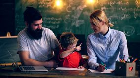 Dos profesores enseñan el muchacho a un plan de estudios de la escuela Proceso de aprendizaje Aprendizaje de concepto Alumnos en  almacen de metraje de vídeo