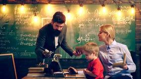 Dos profesores están interesados en la enseñanza de un muchacho Aprendizaje de concepto Alumnos en uniforme Profesor en sala de c metrajes