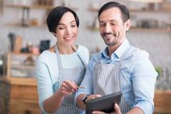 Dos propietarios de negocio en los delantales que se colocan en café Foto de archivo