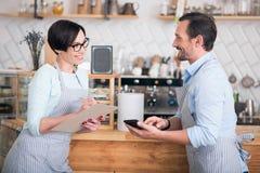 Dos propietarios de negocio en los delantales que trabajan en café Imagenes de archivo