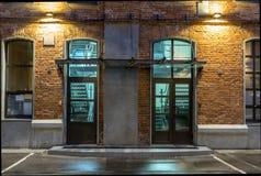 Dos puertas de cristal en un edificio de ladrillo en la noche, casa vieja del ladrillo Opinión de la noche en el viejo distrito i fotos de archivo
