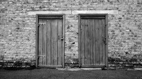 Dos puertas de madera viejas en un edificio de ladrillo imagenes de archivo