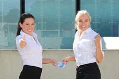 Dos pulgares de las mujeres de negocios para arriba con los billetes de banco euro Foto de archivo