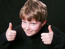Dos pulgares suben al muchacho Imagen de archivo libre de regalías