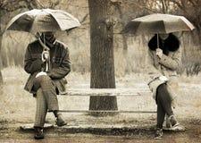 Dos que se sientan en el banco en día lluvioso. imagenes de archivo