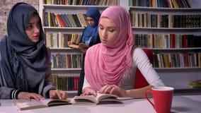 Dos rae concentrados árabes de la mujer del hijab que se sientan en biblioteca en la tabla con el fondo femenino árabe del hijab  metrajes