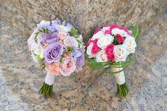 Dos ramos que se casan con las rosas colocadas uno al lado del otro en una piedra de mármol brillante Fotografía de archivo libre de regalías