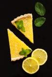 Dos rebanadas de empanada del limón en fondo negro Imagenes de archivo