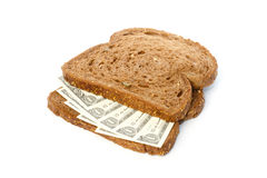 Dos rebanadas de pan con la extensión del bocadillo de los billetes de banco del dólar Imagenes de archivo