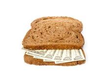 Dos rebanadas de pan con los billetes de banco del dólar intercalan el relleno fotos de archivo libres de regalías