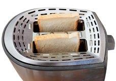 Dos rebanadas de pan frescas en tostadora del metal Imagen de archivo
