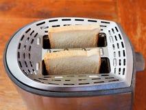 Dos rebanadas de pan frescas en tostadora del metal Imagenes de archivo