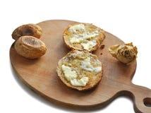Dos rebanadas de pan redondeadas con mantequilla, dos patatas cocidas y una rosa blanca seca en un Chopboard de madera fotos de archivo