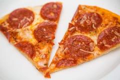 Dos rebanadas de pizza de salchichones en la placa blanca Imágenes de archivo libres de regalías