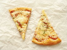 Dos rebanadas de pizza de salchichones recién hecha sobre el pergamino de la hornada Fondo del alimento foto de archivo