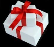 Dos rectángulos de regalo blancos con la cinta roja Fotografía de archivo