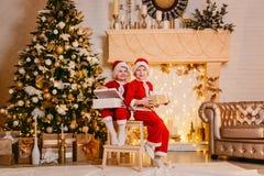 Dos regalos de Navidad abiertos sonrientes del niño foto de archivo