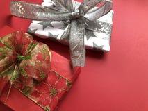 Dos regalos envueltos de lujo de la Navidad en un fondo rojo fotos de archivo libres de regalías