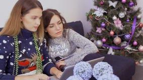 Dos regalos hermosos de la Navidad de las búsquedas de las muchachas en la tienda en línea almacen de metraje de vídeo