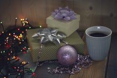 Dos regalos, una taza de café, bola rosada, las luces en el tablen Imágenes de archivo libres de regalías