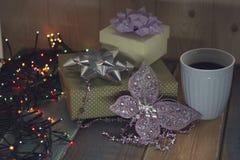 Dos regalos y una taza azul en un de madera tablen Imagen de archivo libre de regalías