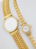 Dos relojes de oro en el fondo blanco Foto de archivo