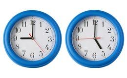 Dos relojes, uno en 9am y uno en 5pm. Fotos de archivo