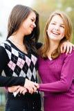 Dos amigas adolescentes que ríen en primavera u otoño al aire libre Imagen de archivo
