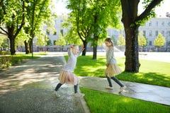 Dos risas y funcionamientos adorables de las hermanas en día de verano caliente y soleado en un parque fotografía de archivo libre de regalías