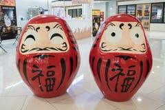 Dos rojo Okiagari Daruma en los grandes almacenes de Ekamai de la entrada fotografía de archivo