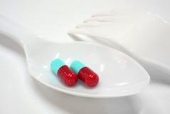 Dos rojos y las cápsulas azules en la cuchara plástica bifurcan Fotografía de archivo