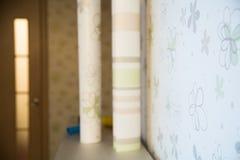 Dos rollos de papel pintado se oponen a la pared con el wallpape floral Fotografía de archivo libre de regalías