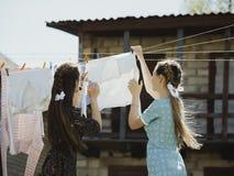 dos ropa seca de las muchachas en la calle foto de archivo