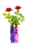 Dos rosas rojas en floreros coloridos Foto de archivo libre de regalías