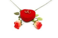 Dos rosas y anillos de bodas son Imagenes de archivo