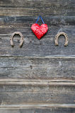 Dos símbolo oxidado de la herradura y del corazón en la pared de madera Foto de archivo