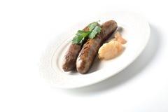 Dos salchichas de la carne con las especias aromáticas en una placa en un fondo blanco fotos de archivo