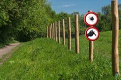 Dos señales de peligro rojas redondas en posts de la cerca delante de un verde Fotografía de archivo