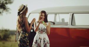 Dos señoras con un buen humor que pasan un rato agradable junto, llevando un vestido retro elegante, por otra parte colocan un he almacen de video