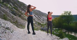 Dos señoras deportivas en el medio del paisaje que sorprendía en la naturaleza pararon para una rotura que parecía lejana para ve metrajes