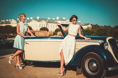 Dos señoras elegantes acercan al coche clásico Fotos de archivo libres de regalías