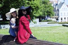 Dos señoras elegantes inclinadas en un banco Foto de archivo libre de regalías