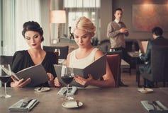 Dos señoras encantadoras con el menú en restaurante Imagenes de archivo