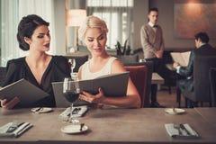 Dos señoras encantadoras con el menú en restaurante Fotografía de archivo libre de regalías