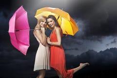 Dos señoras jovenes alegres que presentan en la lluvia Imagen de archivo libre de regalías