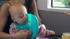 Dos señoras jovenes que alimentan a un bebé en el tren Imagen de archivo