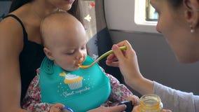 Dos señoras jovenes que alimentan a un bebé en el tren Foto de archivo libre de regalías