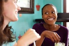 Dos señoras jovenes que charlan en un café fotos de archivo