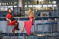 Dos señoras jovenes que se sientan en el contador de la barra Foto de archivo