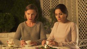 Dos señoras ofendidas que se sientan en el café, no dispuestas a disculparse y a comunicar almacen de metraje de vídeo